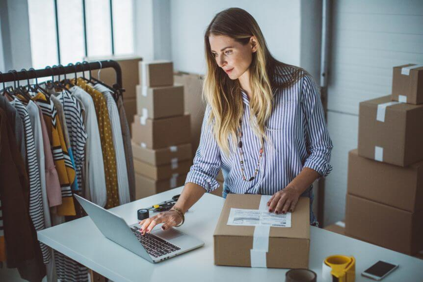 woman-packing-labeled-shipping-packages-and-looking-at-open-laptop